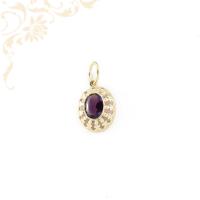 Klasszikus fazonú, női köves arany medál. Közepén lila színű szintetikus kő, oldalát áttört ornamentika díszíti.