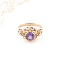 Klasszikus fazonú, női köves arany gyűrű, melynek áttört mintás fejrészét, lila színű szintetikus kő ékesíti