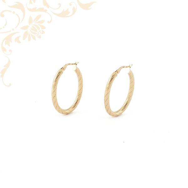 Női arany karika jellegű fülbevaló gyémántvésett mintával díszítve.